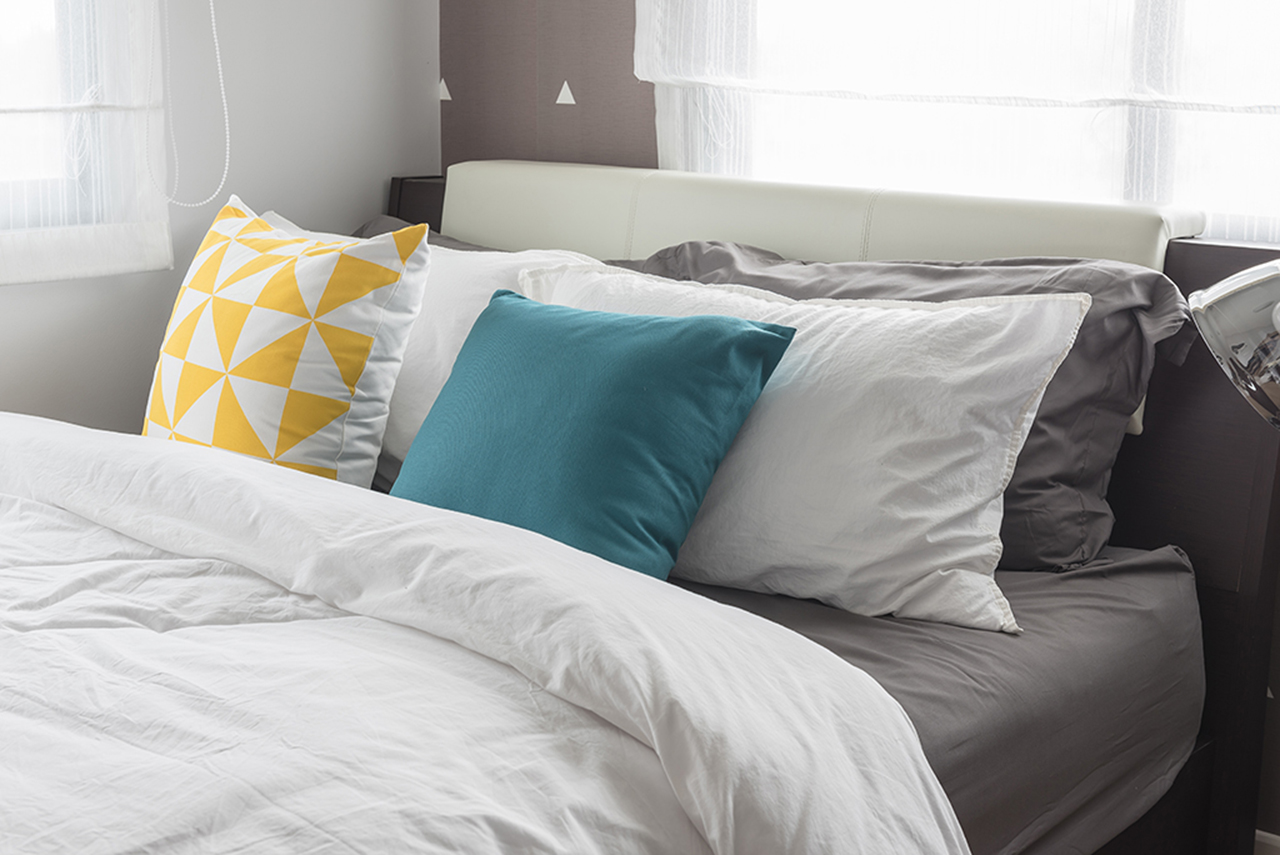 colorful pillows on- white bed in modern bedroom